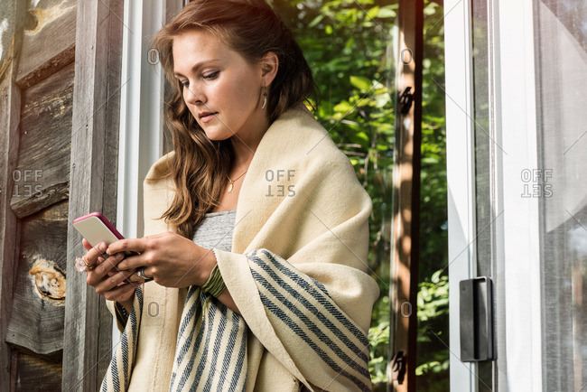 Young woman in porch door with phone