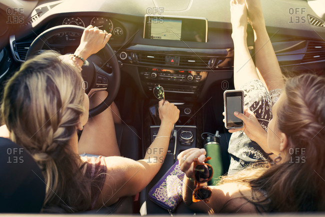 Two women in car with a phone