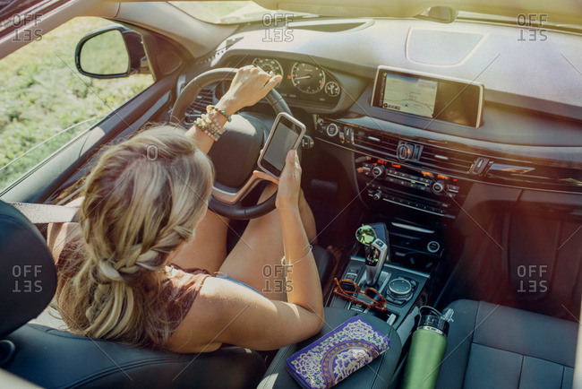 Woman in driver's seat with a phone