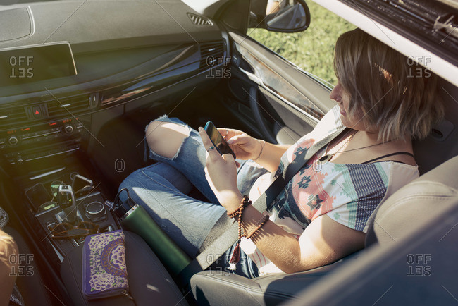 Woman in passenger's seat with a phone