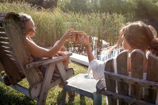 Women with mugs sitting by lake