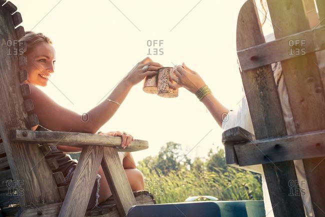 Women toasting sitting by lake