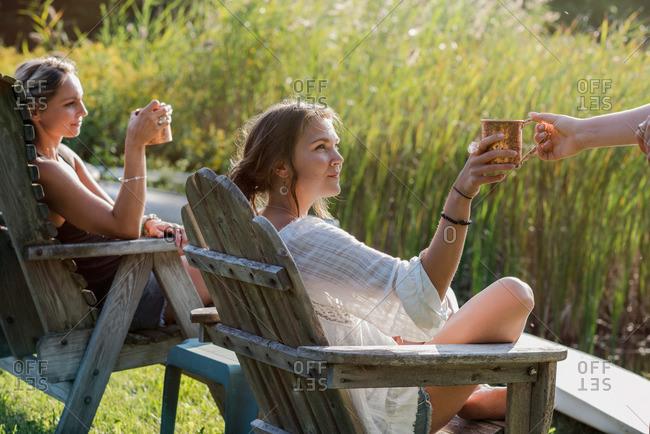 Women having drinks sitting by lake