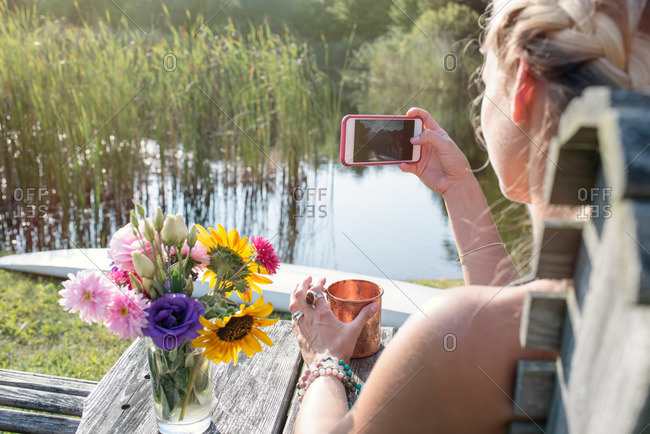Woman taking picture sitting by lake