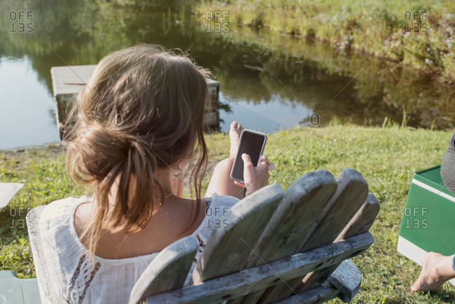 Woman with cell phone relaxing by a lake