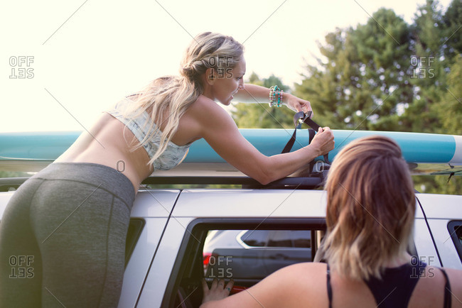 Young women with paddleboard on car