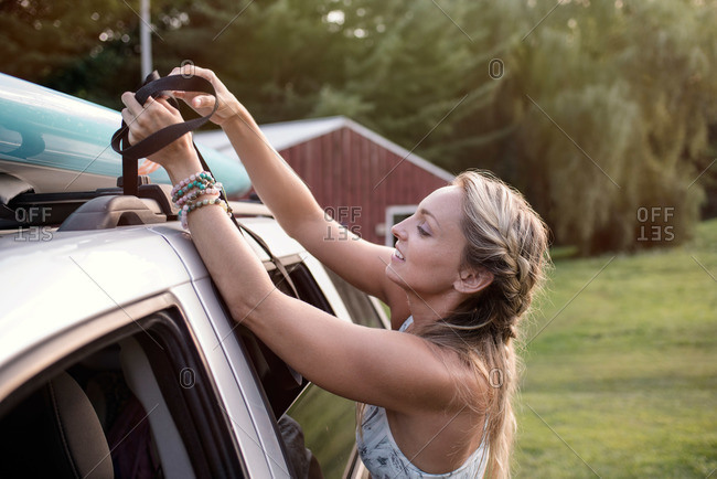 Woman with paddleboard fastened to car