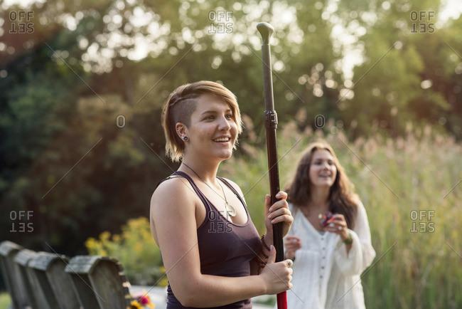 Woman standing with oar near lake