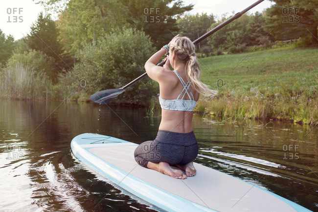 Woman riding paddleboard on lake