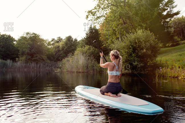 Woman rowing paddleboard on lake