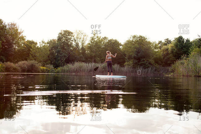 Woman standing on paddleboard in lake