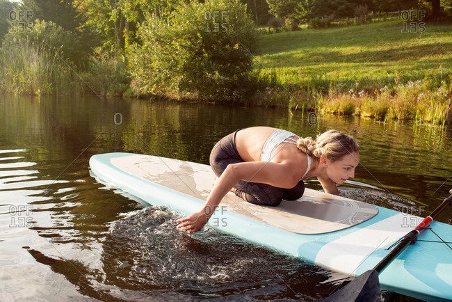 Woman using hands to row paddleboard