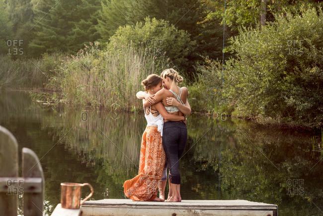 Three women hugging on lake dock