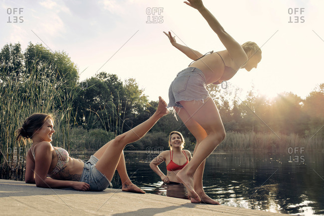Woman jumping into lake by friends