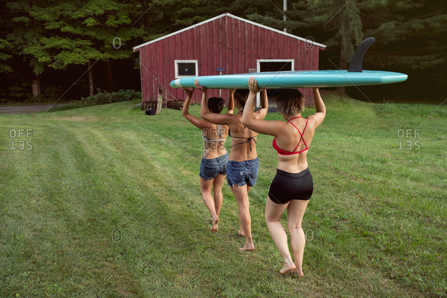 Women carrying a paddleboard in countryside