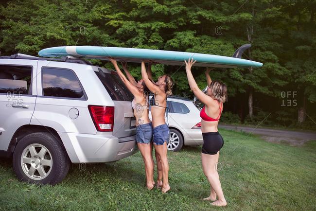 Women putting paddleboard on SUV