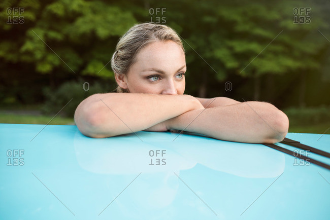 Woman resting on paddleboard on car