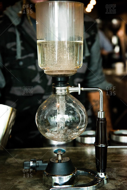 Man brewing coffee in a siphon coffee maker
