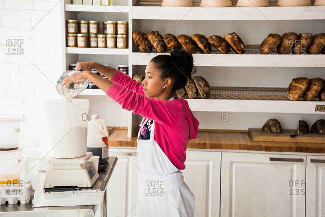 Miami, Florida, USA - September, 2015: Woman scooping flour in a bakery