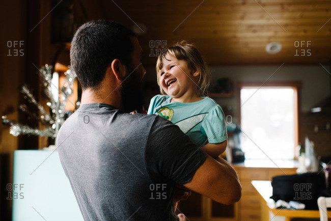 Girl laughing in man's arms in home