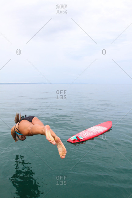 Woman diving into sea by surfboard