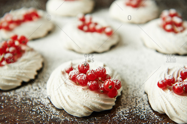 Meringue nests filled with redcurrants and dusted with powdered sugar