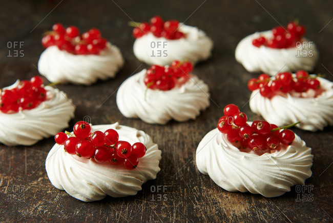 Meringue nests filled with redcurrants on a scratched wooden surface