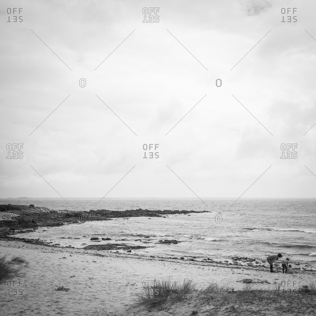 Woman and two children looking closely at objects on the shore line