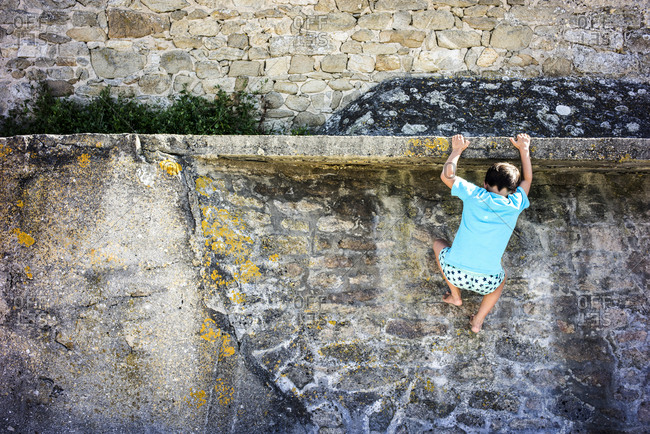 Young boy attempting to climb a rock wall