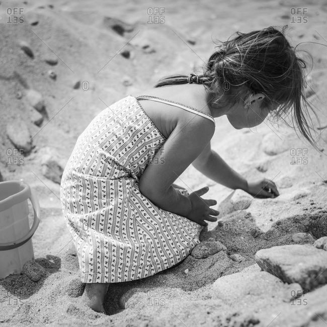 Young girl in sundress digging in the sand