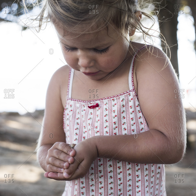 Young girl examining a bug in her hands