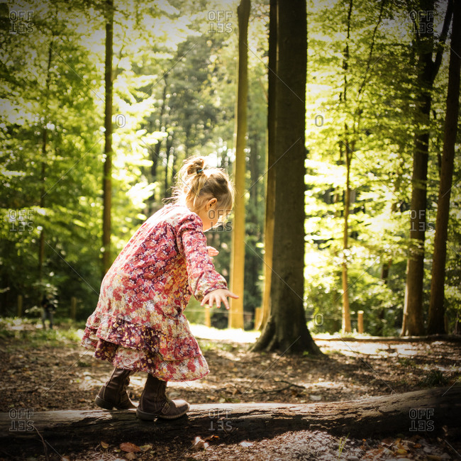 Young girl balancing on a fallen branch