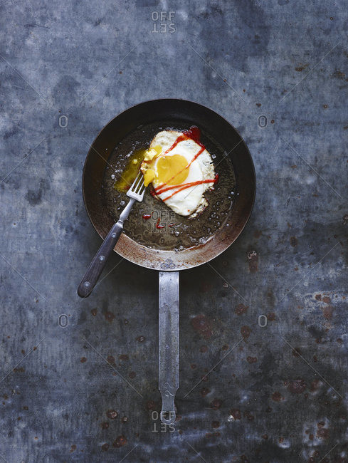 Fried egg in a skillet with hot sauce