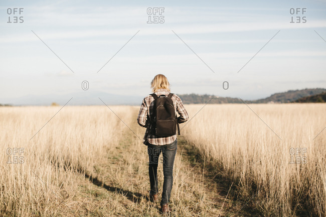 Man walking through a field with a shadow