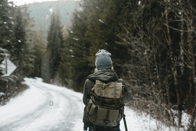 Man standing on a snowy road with a backpack
