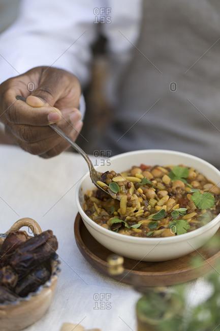 Man eating a bowl of hearty harira