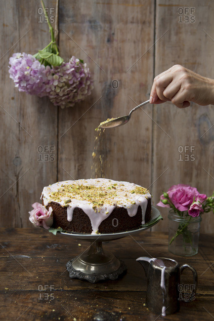 Pistachio and rose cake with hand sprinkling nuts
