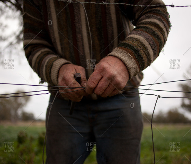 Man repairing wire fence