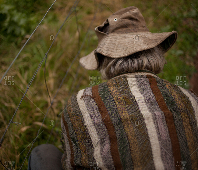 Back view of a senior man with worn sweater and dirty hat repairing his wire fence