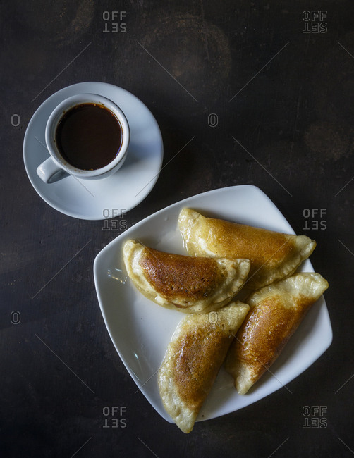 Overhead view of plate of traditional Arab stuffed pancakes with honey and coffee
