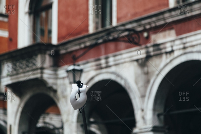 Carnival mask on pole in Venice