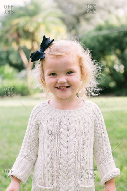 Portrait of cute blond toddler girl in a cable sweater