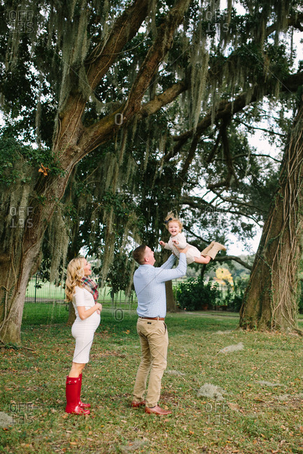 Expectant mother watches as man plays with toddler girl under willow tree