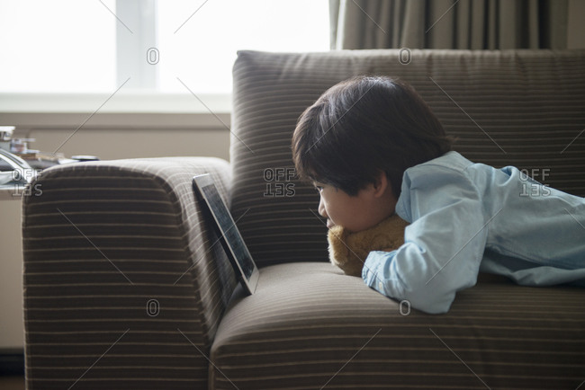 Boy relaxing on couch with a tablet computer
