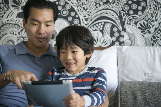 Father and son relaxing at home with a tablet computer