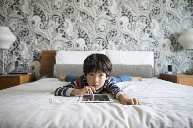 Boy relaxing on a bed with a tablet computer