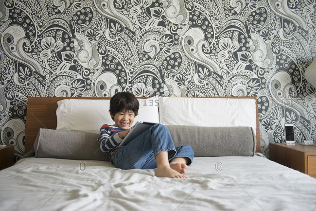 Boy lounging at home using a tablet computer