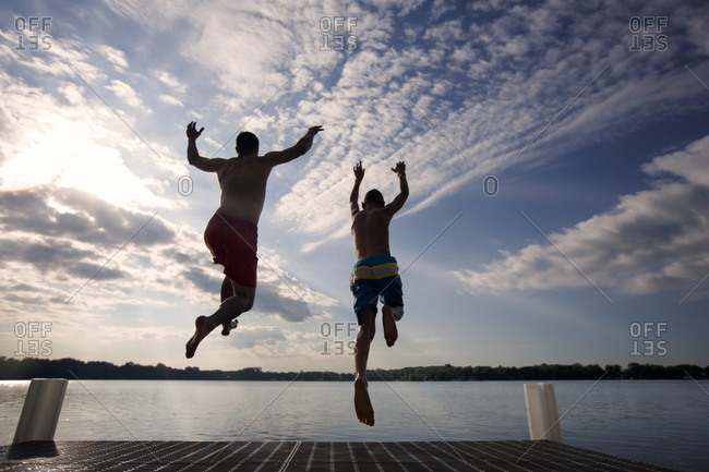 Father and teen son jumping into lake together