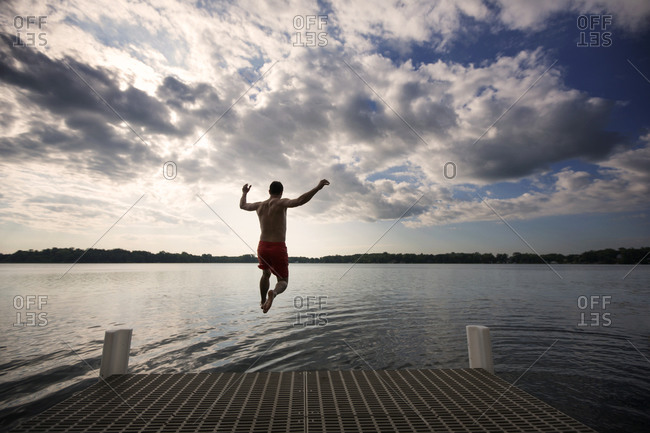 Man jumping off a dock into a lake