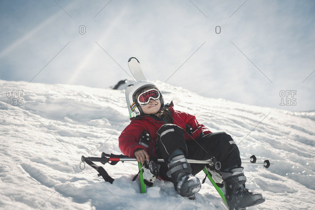 Low angle view of happy girl in ski-wear sitting on snow against sky